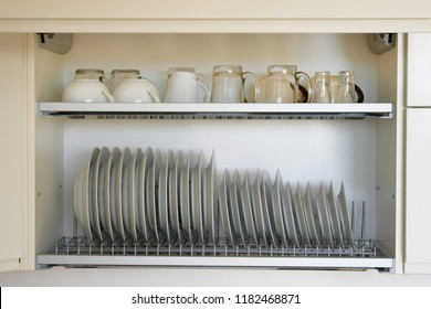 Shelf for tableware drying in modern kitchen. Clean, washed white glass and ceramic dishes on metal rack inside kitchen cupboard.