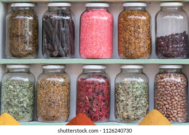 shelf with ten preserving glasses vontaininge herbs and spices