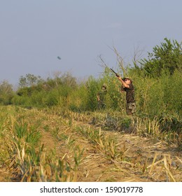 Shell casing flies from shotgun as hunter shoots at dove in a cut corn field.  Dove hunting season begins in September (fall, autumn) in Texas.  Color, square image with room for copy.