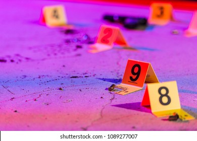 A shell casing is marked with an evidence marker within a crime scene.