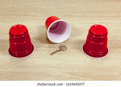 Shell Game - Revealing a key which has been hidden underneath a cup