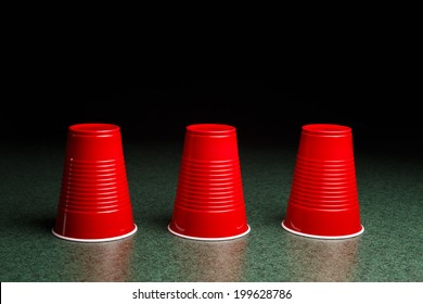 Shell Game - three red cups on a green table arranged like the shell game.  Copy Space.