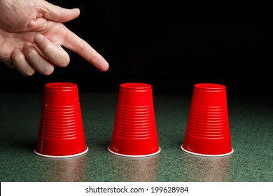 Shell Game - three red cups on a green table arranged like the shell game.  Hand pointing to the center cup.  Copy Space.