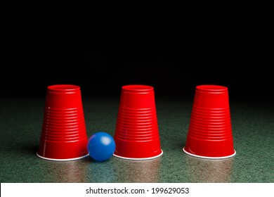 Shell Game - three red cups and a blue ball on a green table arranged like the shell game.  Copy Space.