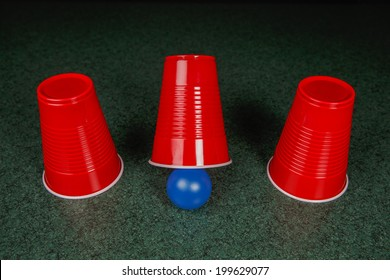 Shell Game - three red cups and a blue ball on a green table arranged like the shell game.  Gambling.  Copy Space.