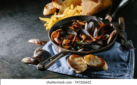 Shell mussels in a frying pan in tomato sauce, French fries and croutons on a dark background.