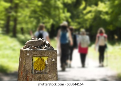 shell scallop sign mark with unfocused pilgrims  in Way of St James , Camino de Santiago, to Compostela, Galicia, Spain