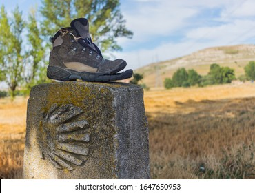 The shell sign of the Camino de Santiago and an old boot of a pilgrim left in the way.