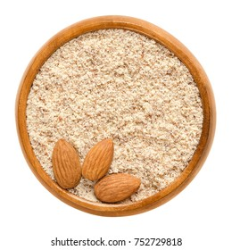 Shelled and ground almond nuts in wooden bowl. Edible, dried, brown seeds of Prunus dulcis. Ingredient in marzipan, nougat, cookies. Isolated macro food photo close up from above on white background.