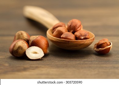 shelled hazelnuts in spoon on wooden background, close up