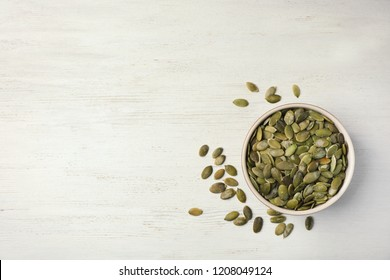 Shelled raw pumpkin seeds on wooden background, top view. Space for text