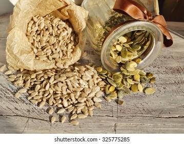 shelled sunflower seeds and pumpkin seeds on a wooden board