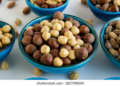Shelled and unshelled luxury hazelnuts in a blue ceramic bowl on white surface