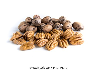 Shelled and unshelled organic pecan nuts on white surface