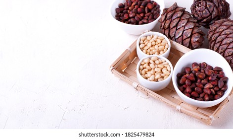 Shelled and unshelled pine nuts and pine cones on the white table. Copy space