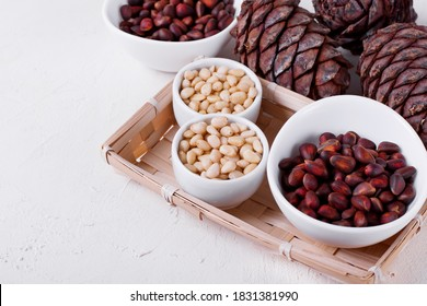 Shelled and unshelled pine nuts and pine cones on the white table