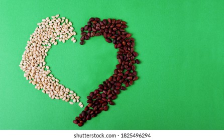 Shelled and unshelled pine nuts are shaping a heart. Concept of beneficial effect of the nuts on cardiovascular system