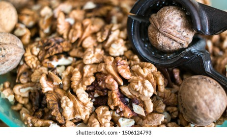 shelled and unshelled walnuts in bowl with nutcracker