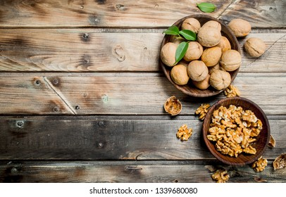 Shelled walnuts in a bowl. On a wooden background.
