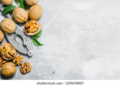 Shelled walnuts with a Nutcracker . On a rustic background.