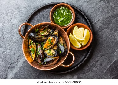 Shellfish Mussels in copper bowl with lemon and herbs sauce. Top view.
