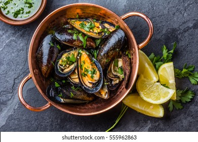 Shellfish Mussels in copper bowl with lemon and herbs. Shellfish seafood. Top view.