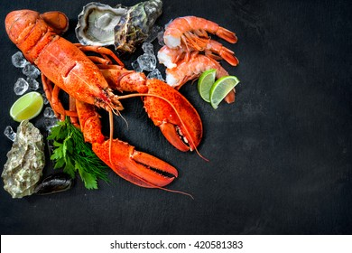 Shellfish plate of crustacean seafood with fresh lobster, mussels, shrimps, oysters as an ocean gourmet dinner background