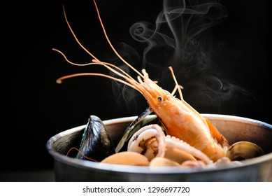 Shellfish seafood plate with shrimps prawns mussel squid ocean gourmet dinner seafood cooked boiled in hot pot with herbs and spices on dark background