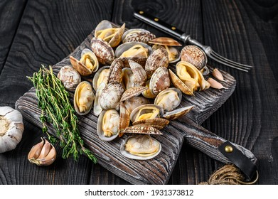 Shells Clams vongole on a wooden cutting board. Black wooden background. Top view.