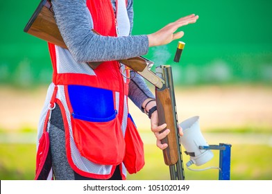 The shells fly out of the shotgun after the shot, The man shoots from the double-barrel shotgun at the sports shooting range, bench shooting at moving targets