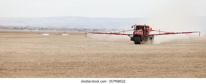 Shelly, Idaho, USA Apr. 1, 2013 A long arm fertilizer spreader putting peleted fertilizer on farm fields.