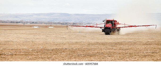 Shelly, Idaho, USA Apr. 1, 2013 A long arm fertilizer spreader putting peletized fertilizer on farm fields.