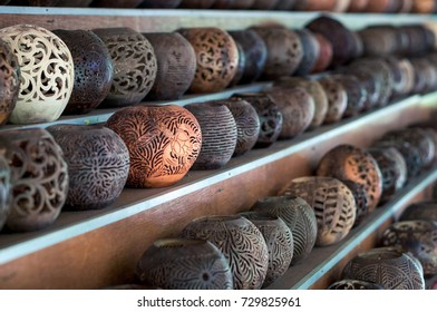 Shelves with balinese souvenirs - ornamental shells for candle wich are carved from the coconut. Traditional product of handicraft on Bali, Indonesia