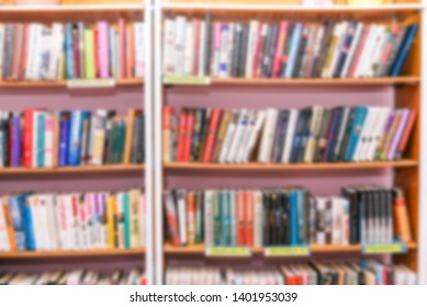 Shelves with books in the library. Blurred background of bookshelves. Education and science. Book store, education and training concept