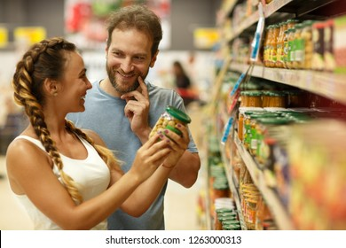 Shelves with cans and tins in supermarket. Woman with braids holding jar and showing it to man. Bearded man smiling and looking at beautiful woman. Couple choosing and buying products together.