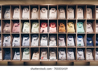 Shelves with a lot of colorful shirts neatly folded in the store clothes and business suits.