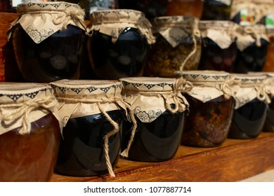 Shelves with composed handmade jam conserved in glass jars and decorated with strings.