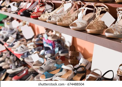 Shelves with fashion shoes are standing in boutique
