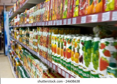 Shelves with fruit juices in boxes in a supermarket in soft focus