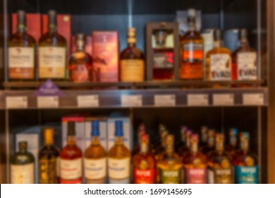 Shelves with a variety of alcoholic drinks in the supermarket. Rich choice. Blurred.