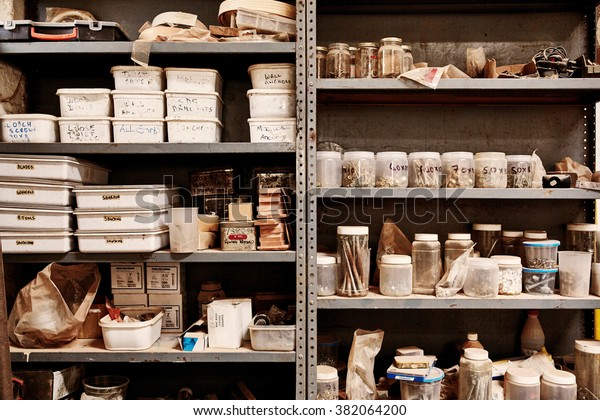 Shelves in a workshop made of a metal unit, with a variety of different plastic containers, jars, boxes and supplies, arranged in neat groups