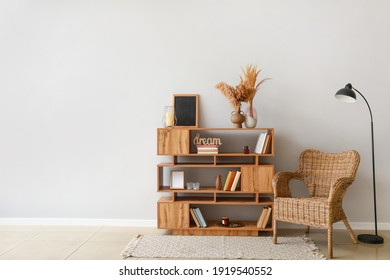 Shelving unit with armchair and lamp in interior of room