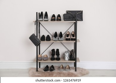 Shelving unit with stylish shoes and purses near white wall. Element of dressing room interior