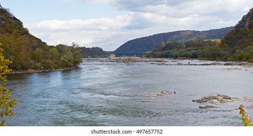 Shenandoah River and Potomac River meet each other near Harpers Ferry, West Virginia, USA. Low river waters with rocks with Appalachian Mountains on horizon.