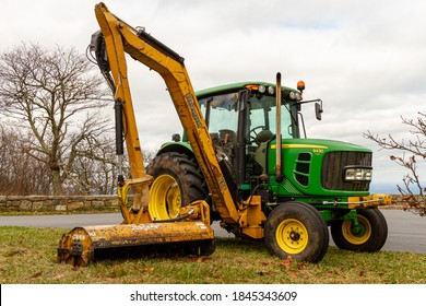 Shenandoah, VA, USA 10/31/2020: A green John Deere model 6430 tractor with A side hydraulic arm attachment (Bengal XR) from Tiger mowers. This attachment is used to trim bushes and cut grass.