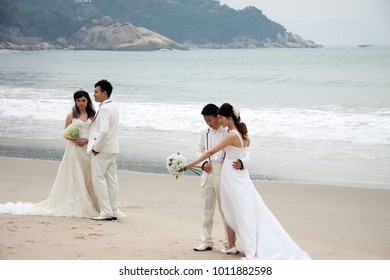SHENZHEN, CHINA, 2011-11-26: Numerous Chinese couples in wedding dresses posing at the beach for their wedding photoshoots