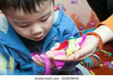SHENZHEN, CHINA, 2011-12-23: Chinese kid blowing confetti from his mom hands at the Christmas party in kindergarten