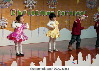SHENZHEN, CHINA, 2011-12-23: Chinese kids in flower costumes performing at improvised stage at kindergarten Christmas party