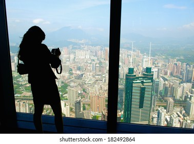 SHENZHEN, CHINA - April 23 2013: Girl takes landscape photo from the highest skyscraper
