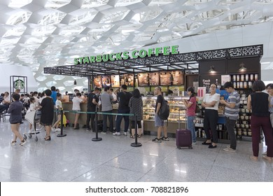 SHENZHEN, CHINA- AUGUST 9, 2017:  People line up at a Starbucks store. Starbucks is company with more than 24,000 stores worldwide.